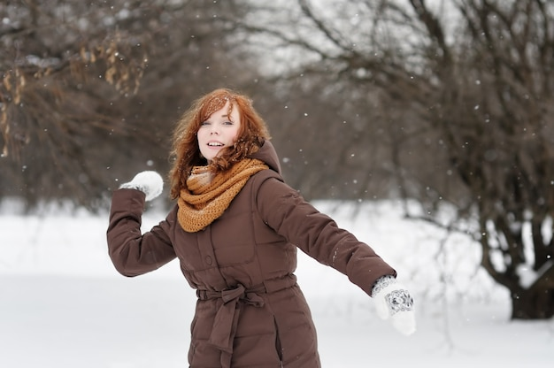 Young beautiful red haired woman having fun in winter