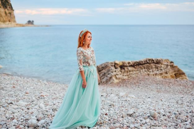 Молодая красивая рыжая женщина в роскошном платье стоит на скалистом берегу адриатического моря