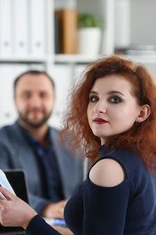 Young beautiful red haired woman sit on chair at table in office in cabinet of her boss hold binder in arms