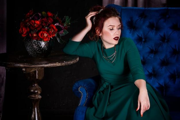 青いソファの上の豪華なインテリアでポーズをとって緑のドレスでプロのメイクと若い美しい赤毛の女性