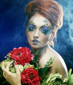 Молодая красивая рыжеволосая женщина с ярким творческим лицом держит цветы