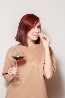 Young beautiful redhaired sommelier with bright lipstick is smelling cork and holding glass of red wine