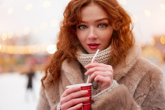 Каток веснушек молодой красивой девушки рыжий дальше. красивая женщина вьющиеся волосы портрет ходить на новогодней ярмарке