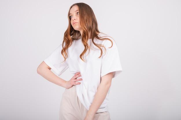 Молодая красивая рыжая женщина в основной одежде, белой футболке и бежевых штанах.