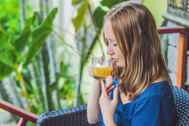 Молодая красивая рыжая женщина сидит в кафе и пьет вкусный утренний имбирный чай в кафе