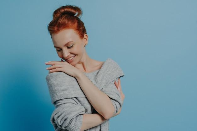 Молодая красивая романтичная рыжеволосая женщина в вязаном свитере с удовольствием обнимает себя и улыбается, чувствуя комфорт, стоя изолированно на синем фоне студии