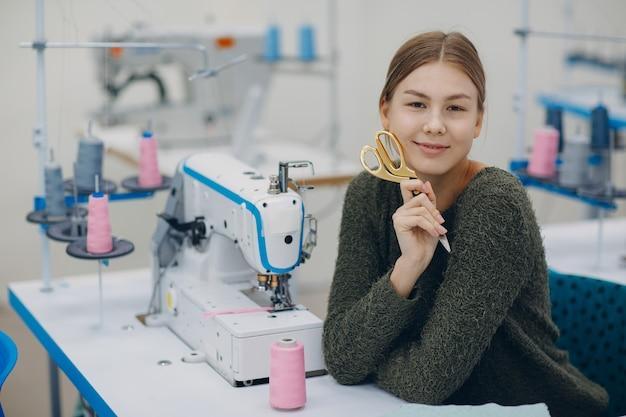 Молодая красивая швея шьет на швейной машине на фабрике.