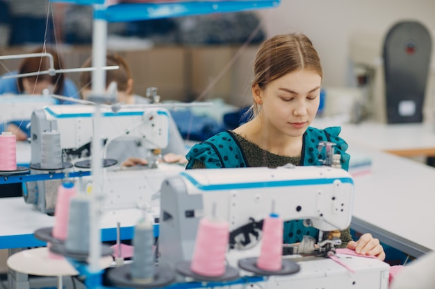 Young beautiful seamstress sews on sewing machine in factory