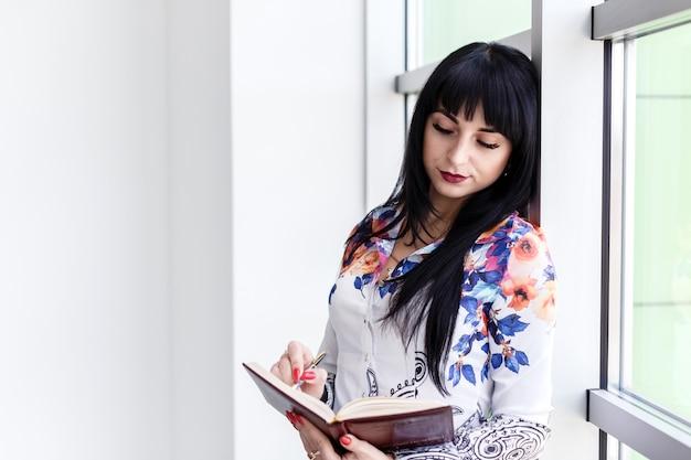 Young beautiful serious woman standing near the window
