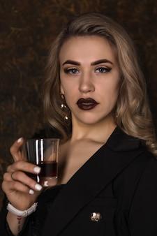 暗い背景にガラスのウイスキーと黒のジャケットと下着の若い美しいセクシーなブロンド