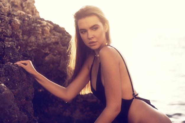 Young beautiful sexy female model in black bikini standing in sea near huge rock