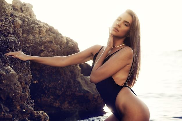 거 대 한 바위 근처 바다에 서 있는 검은 비키니에 젊은 아름 다운 섹시 한 여성 모델