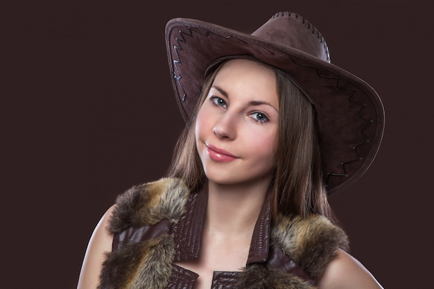 Young beautiful sexy girl in fur waistcoat and cowboy hat