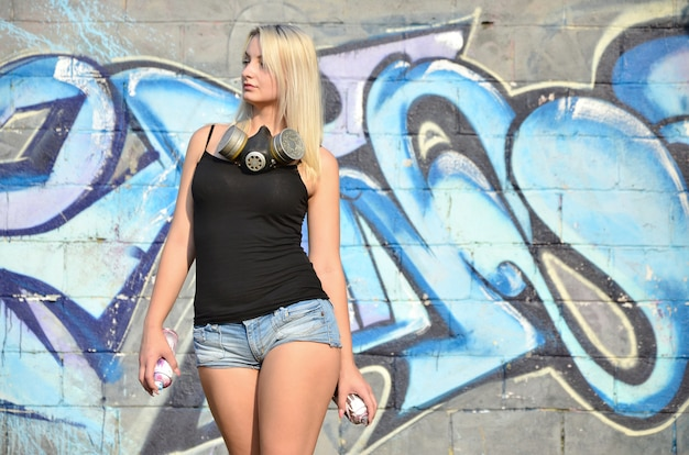 A young and beautiful sexy girl graffiti artist with a paint spray and gas mask