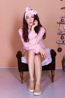 短いピンクのドレスを着た若い美しいセクシーな女の子が自宅の椅子に座っています