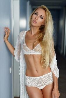 家の壁の周りの下着で若い美しいセクシーな女の子