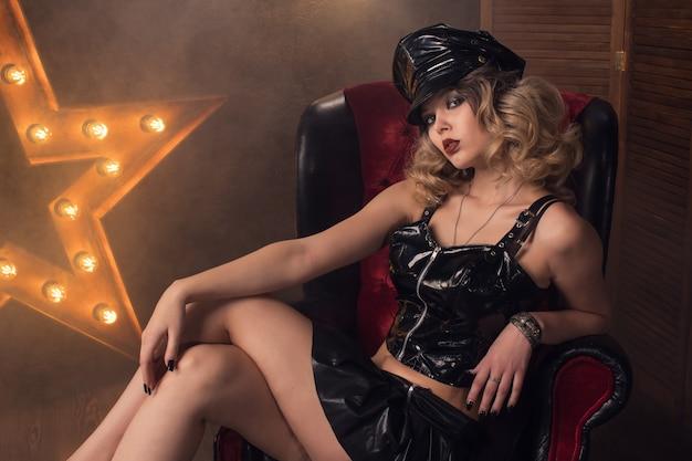 アンティークの椅子とランプと星の背景にフェチドレスラテックスと革のカールを持つ若い美しいセクシーな女の子