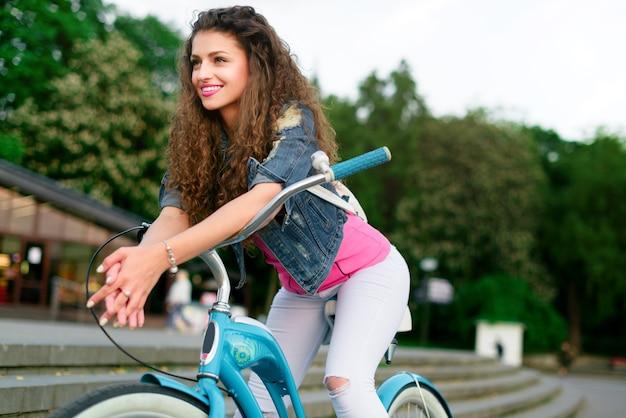 巻き毛と美しい笑顔を持つ若い美しいセクシーな女の子は夏に自転車で公園で休む