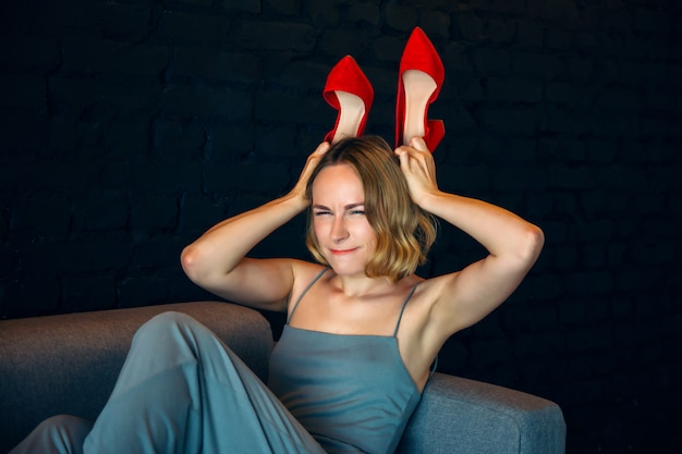 Молодая красивая сексуальная девушка с красными туфлями на диване
