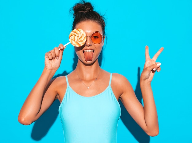 Young beautiful sexy hipster woman with red lips in sunglasses.trendy girl in summer swimwear clothes. positive female going crazy.funny model isolated on blue.eating candy lollipop