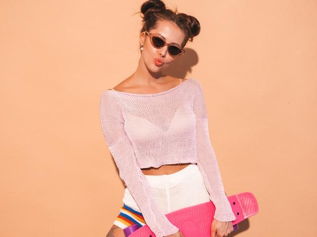 サングラスの若い美しいセクシーな笑みを浮かべて流行に敏感な女性。夏のトレンディな女の子ニットカーディガントピック、ショートパンツ。ベージュの壁に分離されたピンクのペニースケートボードに夢中になるポジティブな女性。