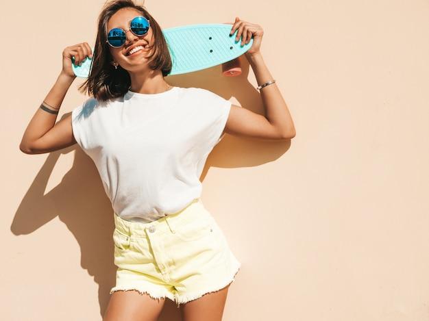 サングラスで若い美しいセクシーな笑みを浮かべて流行に敏感な女性。夏のtシャツとショートパンツでトレンディな女の子。壁の近くの通りでポーズをとって青いペニースケートボードで肯定的な女性
