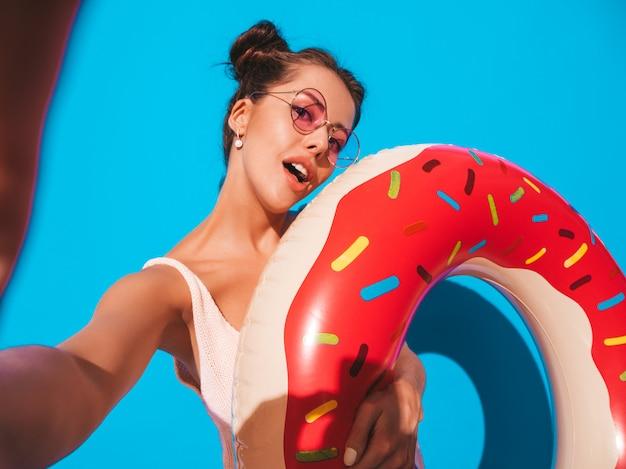 サングラスの若い美しいセクシーな笑みを浮かべて流行に敏感な女性。