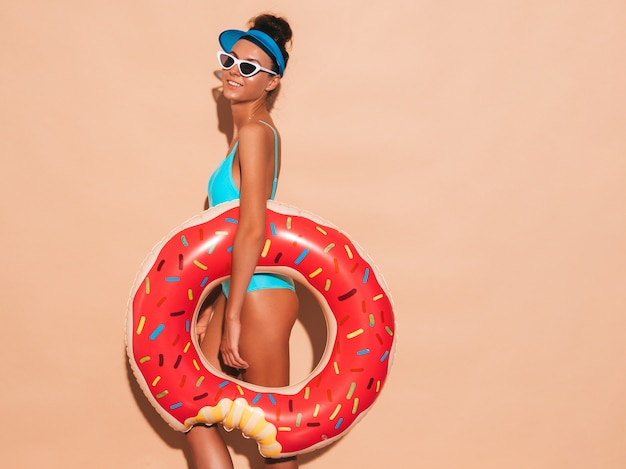 Young beautiful sexy smiling hipster woman in sunglasses.girl in summer swimwear bathing suit with donut lilo inflatable mattress.positive female going crazy.near beige wall in transparent visor cap