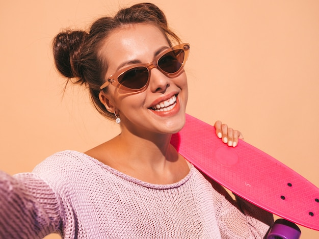 Young beautiful sexy smiling hipster woman in sunglasses.trendy girl in summer knitted cardigan.female with pink penny skateboard,isolated on beige wall.taking selfie self portrait photos on phon