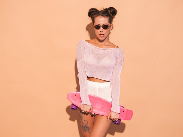 Young beautiful sexy smiling hipster woman in sunglasses.trendy girl in summer knitted cardigan topic ,shorts.positive female going crazy with pink penny skateboard,isolated on beige wall.two hor