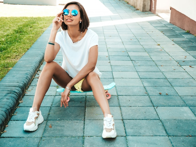 Young beautiful sexy smiling hipster woman in sunglasses.trendy girl in summer t-shirt and shorts.positive female with blue penny skateboard posing on the street background