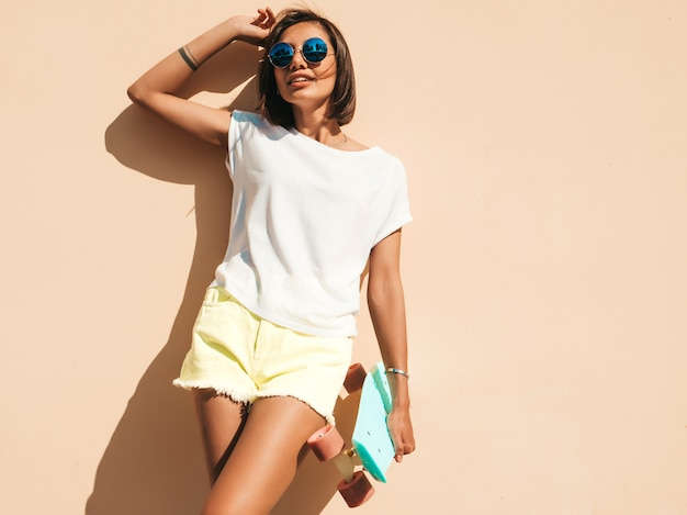 Young beautiful sexy smiling hipster woman in sunglasses.trendy girl in summer t-shirt and shorts.positive female with blue penny skateboard posing in the street near wall