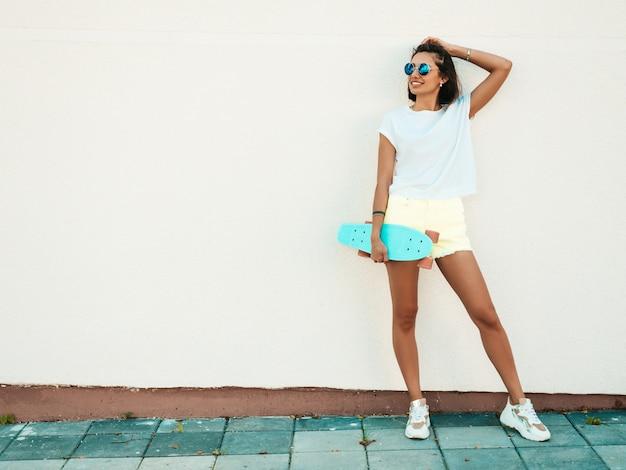 Giovane bella donna sorridente sexy dei pantaloni a vita bassa in occhiali da sole. ragazza alla moda in maglietta e shorts di estate. femmina positiva con il pattino blu del penny che posa nella via vicino al muro bianco