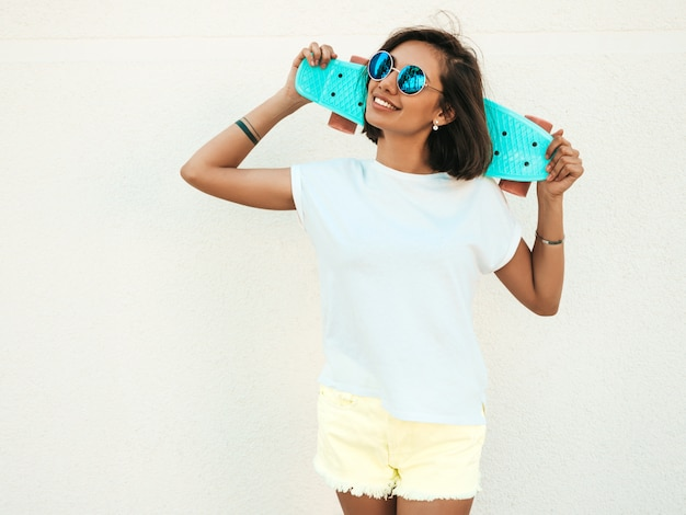 Young beautiful sexy smiling hipster woman in sunglasses.trendy girl in summer t-shirt and shorts.positive female with blue penny skateboard posing in the street near white wall