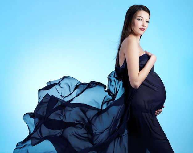 Young beautiful sexy and stylish  pregnant woman in blue - blue space