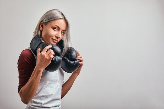 灰色の背景に彼女の手で黒いボクシンググローブでポーズをとる若い美しいセクシーな女性ボクサー。コピースペース、灰色の背景、目標達成。