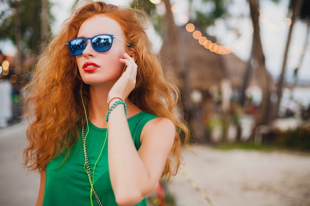 Young beautiful sexy woman, hipster style, red hair, traveler, green top, orange suitcase, summer vacation, traveling, sunglasses, listen music, earphones, sunglasses, tropical trip