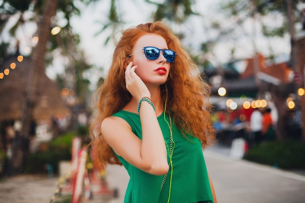 若い美しいセクシーな女性、流行に敏感なスタイル、赤い髪、旅行者、緑のトップ、オレンジ色のスーツケース、夏休み、旅行、サングラス、音楽を聴く、イヤホン、サングラス、熱帯旅行