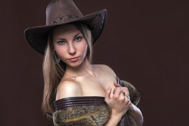 Молодая красивая сексуальная женщина в меховом жилете и ковбойской шляпе