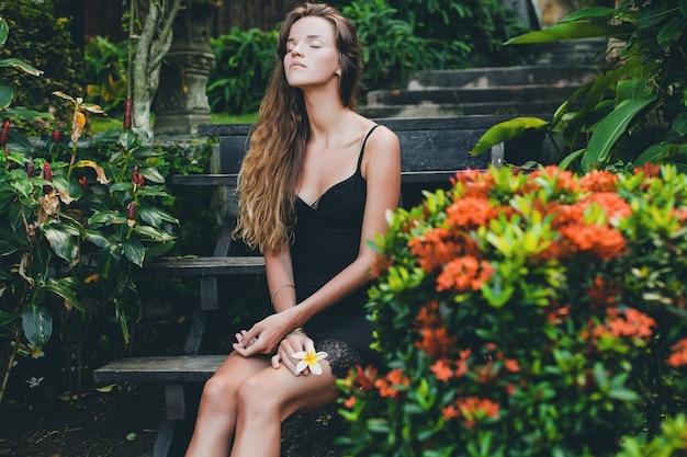 열대 정원에서 젊은 아름다운 섹시한 여자, 태국의 여름 휴가, 날씬한 스키니 그을린 몸, 레이스가있는 작은 검은 드레스, 자연스러운 표정, 관능적 인, 편안한,