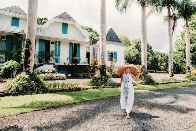 熱帯の島の若い美しいセクシーな女性。白いロングドレスと大きな麦わら帽子のスタイリッシュな女の子。モーリシャスの幸福の夏休み。植民地時代の家を背景に