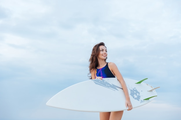 Young beautiful sexy woman in swimsuit holding surfboard the beach