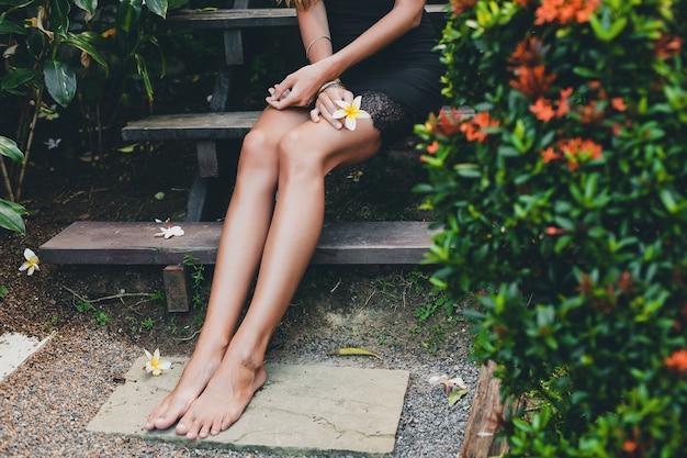 Giovane bella donna sexy in giardino tropicale, vacanze estive in thailandia, corpo sottile e magro abbronzato, tubino nero con pizzo, aspetto naturale, sensuale, rilassato, gambe da vicino i dettagli