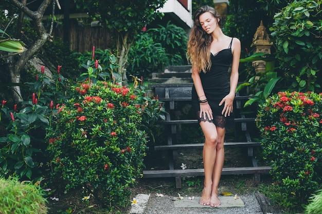 Giovane bella donna sexy in giardino tropicale, vacanze estive in thailandia, corpo abbronzato magro, vestitino nero con pizzo, aspetto naturale, sensuale, rilassato,