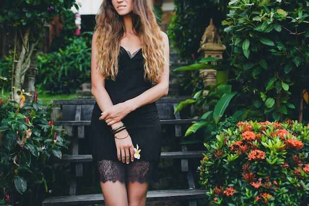 Young beautiful sexy woman in tropical garden, summer vacation in thailand, slim skinny tanned body, little black dress with lace, sensual, relaxed, holding flower in hand, close up details
