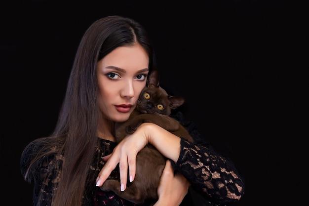 Молодая красивая сексуальная женщина с ярким макияжем с кошкой в руках