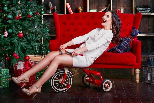 거의 크리스마스 트리에 가까운 아이 자전거를 타고 하얀 드레스를 입고 젊은 아름다운 외치는 매력적인 여자