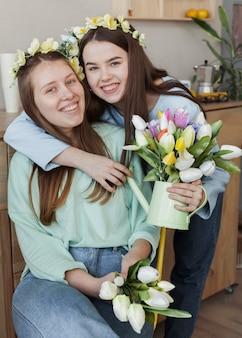チューリップの花を保持している若い美しい姉妹
