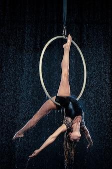 Молодая красивая стройная артистка цирка исполняет представление с воздушным обручем, позирует на черном фоне аквастудии.