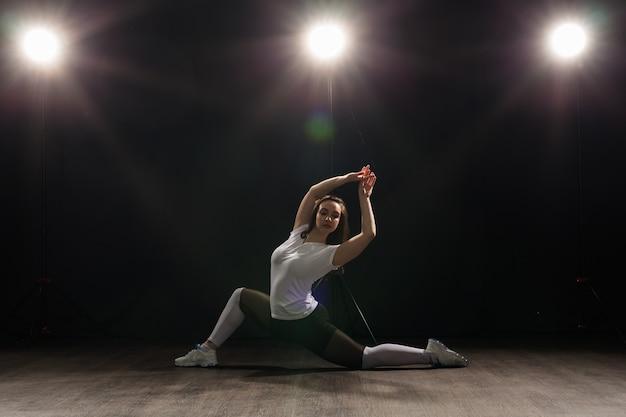 Young beautiful slim woman dancing jazz-funk on a black studio background.